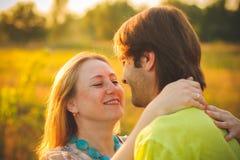 Fira smekmånad romantiskt förälskat för par på fält- och trädsolnedgången Lyckliga barnpar för nygift person som omfamnar tycka o Royaltyfri Fotografi