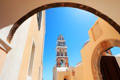 Fira town Church Clock Tower framed by an Arch way.Santorini island Cyclades in Greece. Blue sky background Royalty Free Stock Photo