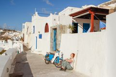 Fira town street with white houses and a white tourist with glasses sits with her back to the wall next to a motorcycle stock image