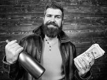 Fira vinst Brutal skäggig hipster för man att bära alkohol för drink för pengar för kassa för håll för läderomslag Svart olaglig  royaltyfri bild