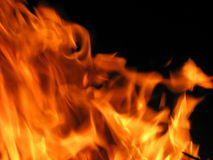 Fire. Flames raising in a dark background Stock Images