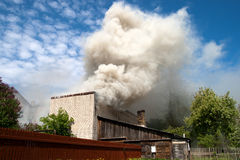 Fire. In city building, with white smoke to the blue sky stock image