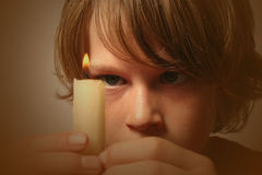 Fire. Boy staring intently at a burning candle he is holding Stock Image