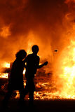 FIRE!. Man and wife in front of a huge fire Stock Image