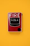 Fire alarm. On yellow wall Stock Photos