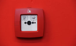 Fire alarm. System button on red wall Royalty Free Stock Images