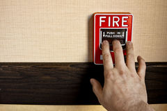 Fire Alarm Activate. Many buildings have manual fire alarm boxes. A man's hand is on the alarm lever to activate it. There is room for your copy on the stock image