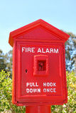 Fire Alarm Box. Fire alarm red box shown outside with green bushes and blue sky background Royalty Free Stock Images