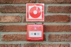 Fire alarm button in emergency system over a wall. Fire alert. Fire alarm button in emergency system over a wall stock photo