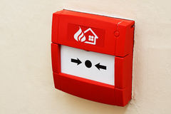 Fire alarm button on wall. Wall mounted Red fire alarm button used to activate warning systems in buildings stock images