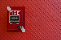 Manual hand pull Fire alarm red red background. Fire alarm hand lever red on red diamond steel background Stock Image