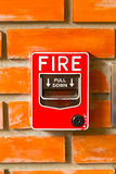 Fire Alarm Switch on the brick wall background texture. Royalty Free Stock Photos