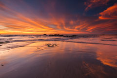 Fire alike sky with reflection on the white sand Stock Images