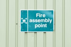 Fire assembly point sign on green container construction site royalty free stock images