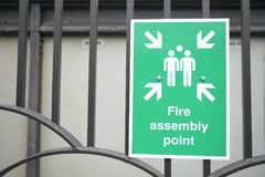 Fire assembly point sign at workplace car park fence Stock Photography