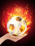 Fire Ball hold in the hand. On red background Royalty Free Stock Images