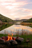 Fire on bank of lake. A fire sits nestled next to a lake overlooking a sunset Stock Photos