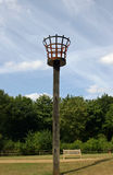 Fire beacon in a park. Fire beacon on a wooden pole set in lawns in a park with trees, bench and blue sky with white clouds behind Stock Photo