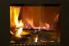 Fire behind the glass in a closed fireplace stock image