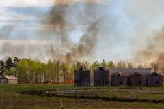 Fire behind log grain bins royalty free stock photography