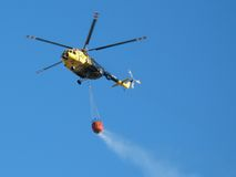Fire-bird in flight. Landscape photo of a fire-fighting helicopter in flight royalty free stock photos