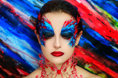 Fire bird. Young beautiful woman lady model woman character butterfly bird firebird ice queen. Creative perfect fantasy makeup. Bright saturated colors red blue Stock Images