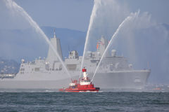 Fire-boat with Naval Ship. Fire-boat sprays water to welcome a naval ship to San Francisco Bay Royalty Free Stock Photo