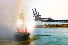 Fire boat show. Fire fighting boat sprays water in port Royalty Free Stock Photos