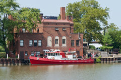 Fire Boat. A fire boat used to protect the waterfront along the Cuyahoga River and the port of Cleveland, Ohio sits moored next to a riverfront fire station Royalty Free Stock Photography