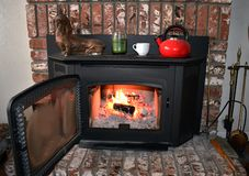Fire in brick fireplace and mantle inside a cozy family room royalty free stock image