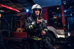 Fireman in a protective uniform standing next to a fire truck and talking on the radio. The fire brigade arrived at the. The fire brigade arrived at the night stock photography