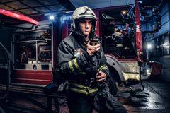 Fireman in a protective uniform standing next to a fire truck and talking on the radio. The fire brigade arrived at the. The fire brigade arrived at the night royalty free stock photo