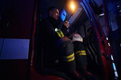 The fire brigade arrived at the night-time. Fireman sitting in the fire truck and talking on the radio. The fire brigade arrived at the night-time. Fireman in a stock image