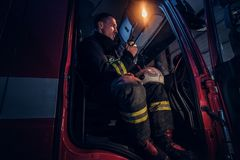 The fire brigade arrived at the night-time. Fireman sitting in the fire truck and talking on the radio. The fire brigade arrived at the night-time. Fireman in a stock photography