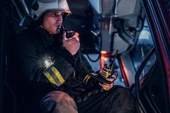 The fire brigade arrived at the night-time. Fireman sitting in the fire truck and talking on the radio. The fire brigade arrived at the night-time. Serious royalty free stock photos