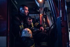 The fire brigade arrived at the night-time. Fireman sitting in the fire truck and talking on the radio. The fire brigade arrived at the night-time. Serious stock photography