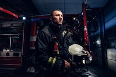 The fire brigade came to the call at night. Handsome fireman wearing a protective uniform with a flashlight included. Holding a helmet and looking sideways stock photography