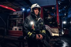 The fire brigade came to the call at night. Handsome fireman wearing a protective uniform with a flashlight included. Holding a helmet and looking sideways stock photos