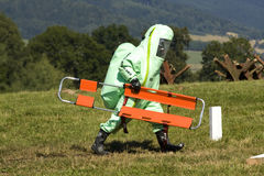 Fire brigade. In chemical protection suit firefighter carries a stretcher Stock Photography