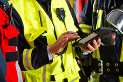 Fire brigade deployment plan on Tablet Computer. Fire brigade - Squad leader gives instructions, he used the Tablet Computer to plan the deployment Royalty Free Stock Photography