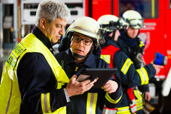 Fire brigade deployment planning on Computer. Fire brigade - Squad leader gives instructions, he used the Tablet Computer to plan the deployment Royalty Free Stock Photography