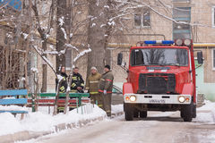 Fire Brigade are at the entrance of an apartment building, standing next to a fire service vehicle Royalty Free Stock Photography