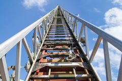 Fire brigade ladder into a blue sky with white clouds Royalty Free Stock Image