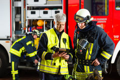 Fire brigade deployment planning. Fire brigade - Squad leader gives instructions, he used the Tablet Computer to plan the deployment Stock Photography