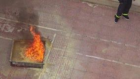 Fire Brigade Training Man Burns out Model Fire Plot. NHA TRANG, KHANH HOA/VIETNAM - MAY 28 2016: Closeup upper view practical training of fire brigade man burns stock footage