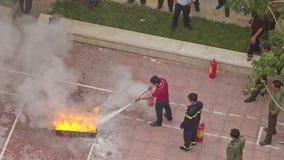 Fire Brigade Training Man Extinguishes Model Fire Plot. NHA TRANG, KHANH HOA/VIETNAM - MAY 28 2016: Upper view practical training of fire brigade man stock video