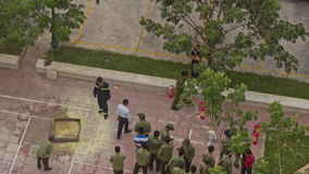 Fire Brigade Training Men Form in Column near Extinguishers. NHA TRANG, KHANH HOA/VIETNAM - MAY 28 2016: Upper view practical training of fire brigade men in stock video footage