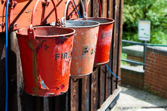 Fire buckets. A collection of three fire buckets at a steam railway station Stock Images