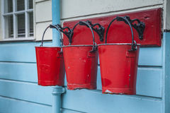 Fire buckets. Red fire buckets on a blue wall Stock Images