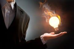 Fire bulb. Business man holding fire light bulb Stock Photos